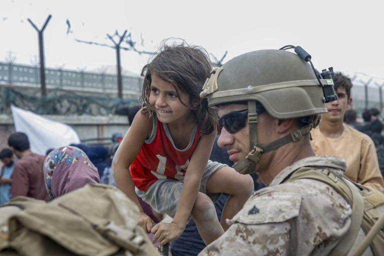 Un marine junto a una pequeña afgana