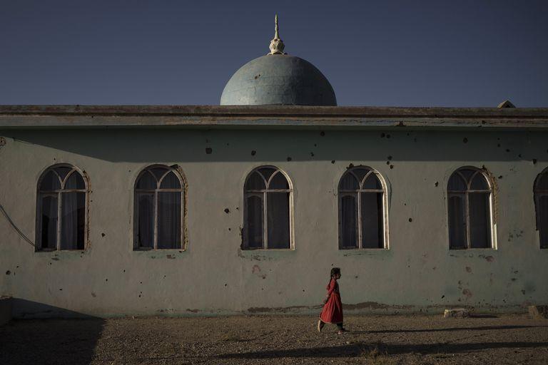 Una niña afgana camina junto a una mezquita en una aldea en la provincia de Wardak, Afganistán, el 11 de octubre del 2021. (AP Foto/Felipe Dana)
