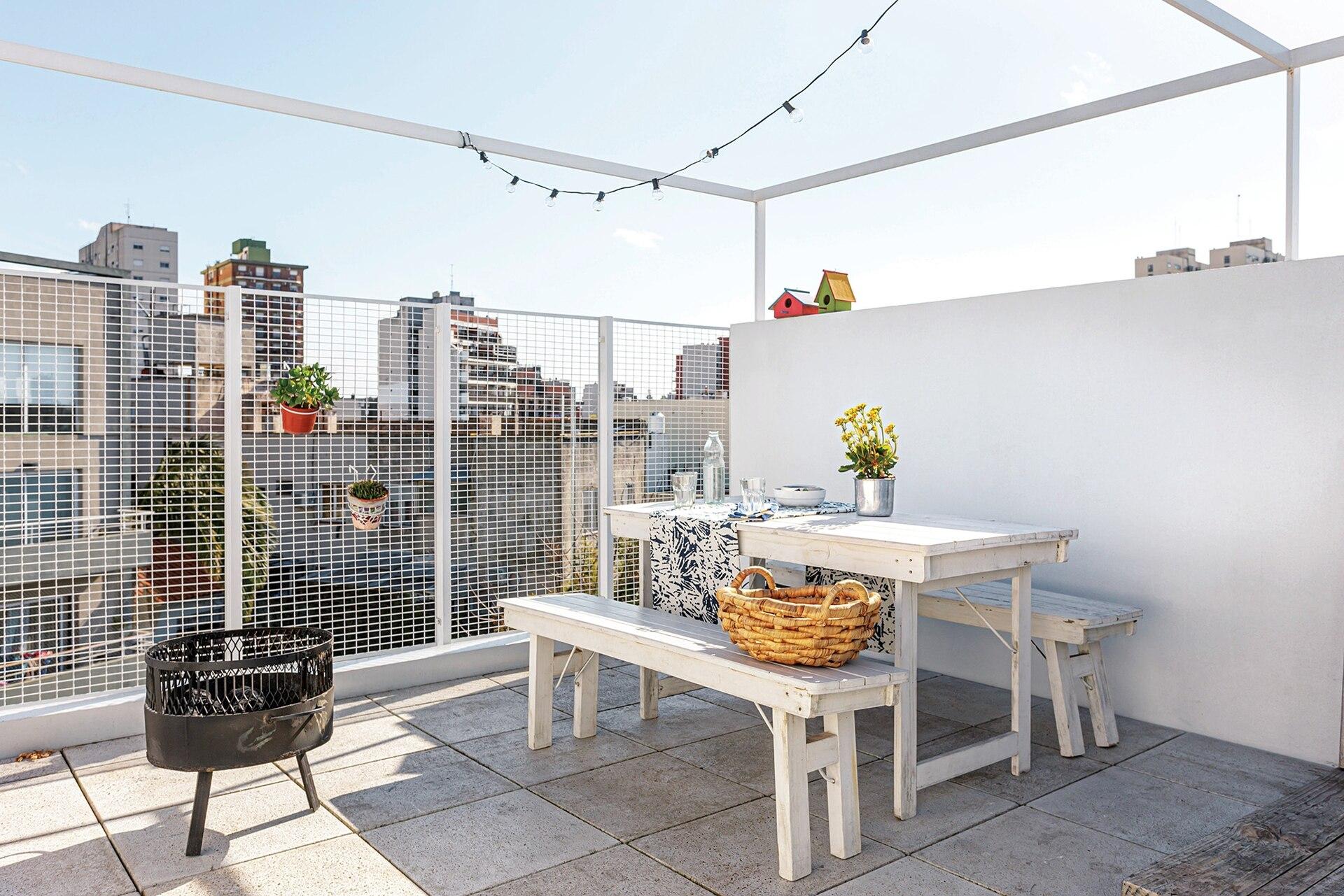 En la terraza, juego de mesa y bancos plegables. Cesto de fibras naturales (Claudia Adorno). Mantel estampado (Petite Margot).