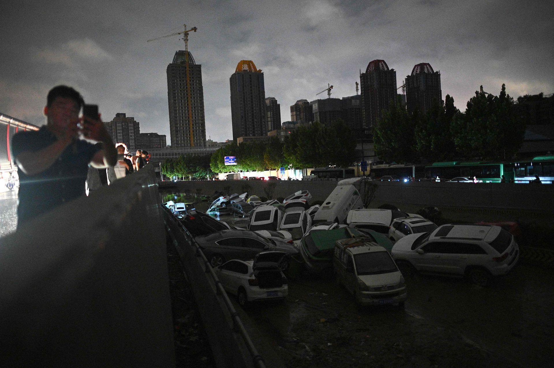 La gente mira los autos sumergidos en un paso subterráneo luego de las fuertes lluvias en Zhengzhou, en la provincia china de Henan