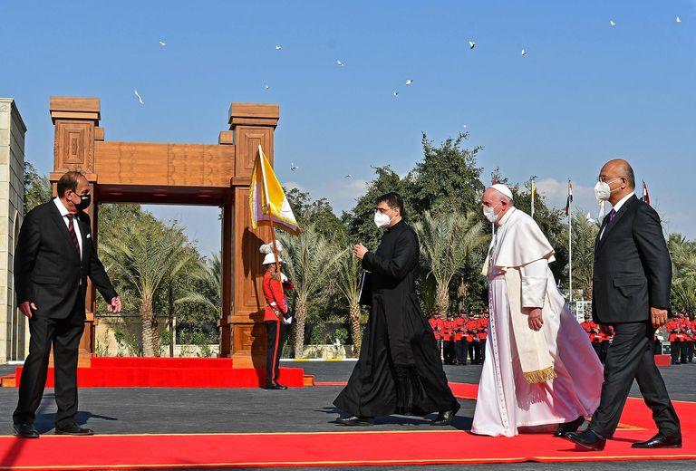 El Papa Francisco camina junto al presidente iraquí, Barham Saleh, durante una ceremonia de bienvenida en el palacio presidencial en Bagdad