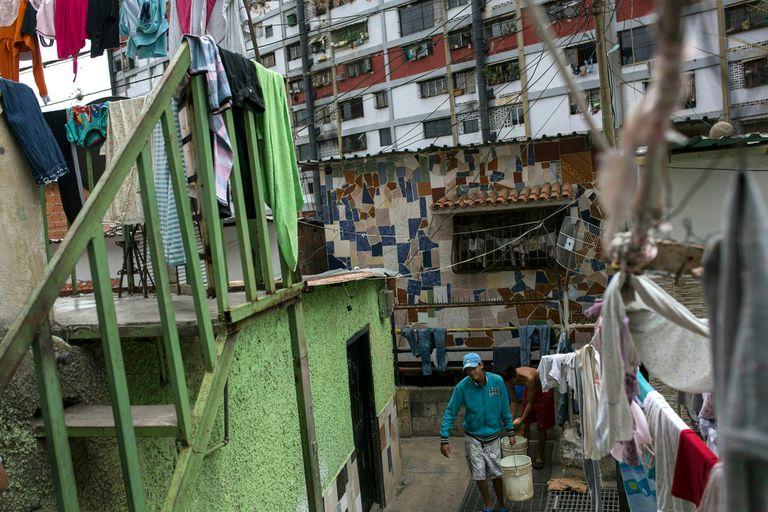Un hombre carga un balde de agua hacia su casa, en un barrio de la capital venezolana