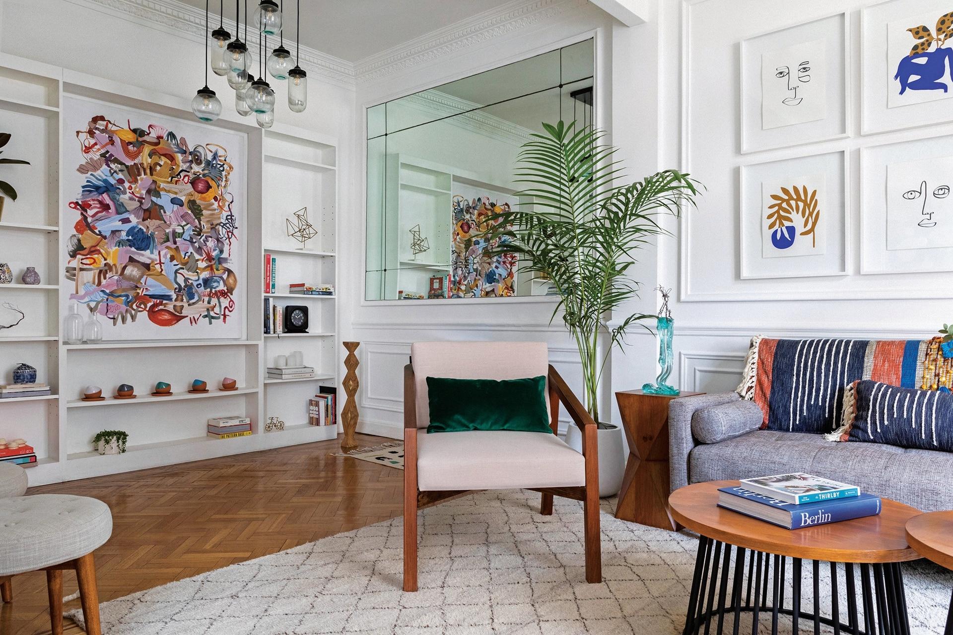 Mesas ratonas, sillón individual (ambos, diseñados por Caro Yañez) con almohadón en pana verde (De Levie). Espejo original del edificio, lámpara de techo (Pottery Barn) y areca con maceta 'Gota' (Ciudad Naturaleza). Casi al corte, banquito de madera con asiento en capitoné (West Elm).