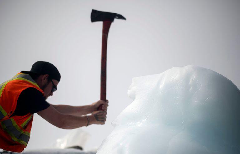 Taylor Lindsorn saca hielo con su hacha de un iceberg en la Bahía de Bonavista el 30 de junio de 2019 en Terranova, Canadá