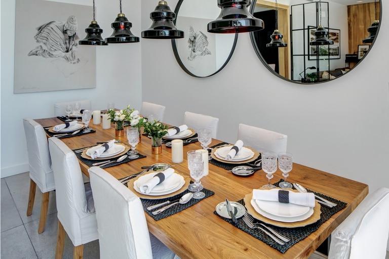 Una mesa impecable, iluminada por cuatro lámparas de vidrio de Negro House Pleasures, con platos que María trajo de un viaje y copas de cristal de Bohemia, regalo de su casamiento. Sobre la pared, dos espejos de hierro. En uno de ellos asoma un cuadro de la artista plástica Catalina Scoppa.