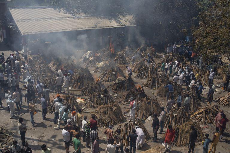 ARCHIVO - En esta imagen de archivo del 24 de abril de 2021, varias piras funerarias de fallecidos por el COVID-19 arden en un terreno convertido en crematorio para la incineración masiva de víctimas de coronavirus en Nueva Delhi. El exceso de mortalidad en India durante la pandemia podría ser 10 veces la cifra oficial de víctimas del COVID-19, lo que probablemente lo convertiría en la peor tragedia de la India moderna en pérdida de vidas humanas, según el estudio más profundo hasta la fecha sobre los estragos del virus en el país del sur de Asia. (AP Foto/Altaf Qadri, Archivo)