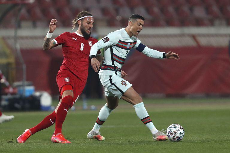 El serbio Nemanja Gudelj y el portugués Cristiano Ronaldo luchan por el balón durante el partido de clasificación del grupo A para la Copa Mundial 2022 entre Serbia y Portugal en el estadio Rajko Mitic en Belgrado, Serbia, este sábado.