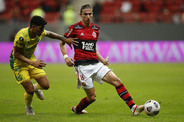 Filipe Luis mide el pase ante la marca de Lautaro Escalante; en Brasilia y ante 18 mil espectadores, Flamengo demostró contundencia para vapulear en el resultado a Defensa y Justicia