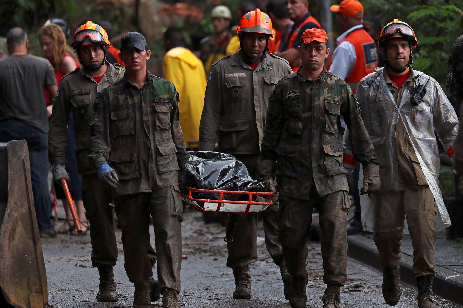 Los rescatistas se llevan cuerpos en el sitio de un alud, después de fuertes lluvias