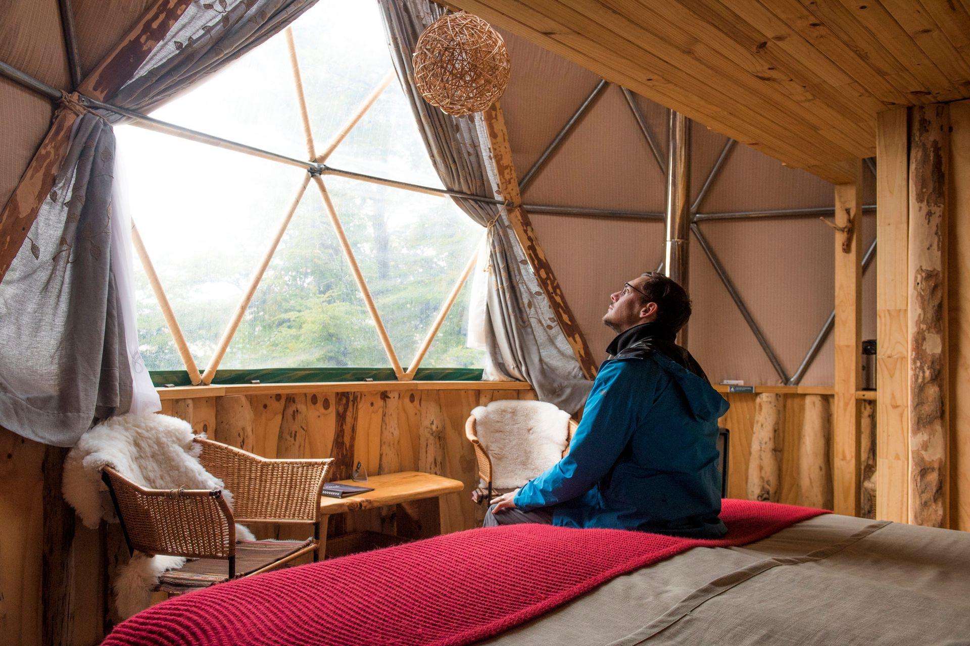 El interior de uno de los domos, con cama, baño, alfombras, sillones mullidos y vista privilegiada.