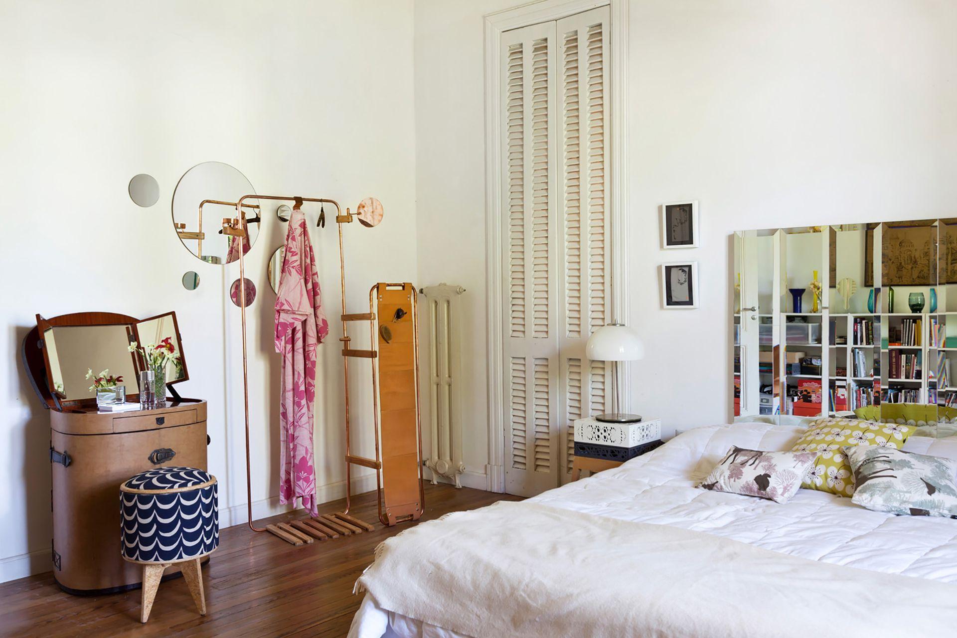 """En el dormitorio principal, la cama baja se coronó con un panel de espejos biselados que duplican el espacio. El perchero pertenece a la serie """"Lynko""""."""