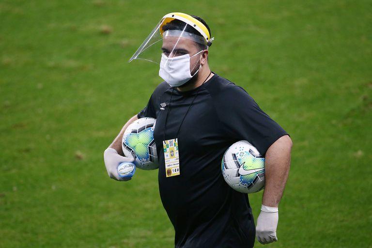 Un miembro del personal del torneo brasileño con una máscara protectora, luego de la reanudación del juego a puerta cerrada después del brote de la enfermedad por coronavirus