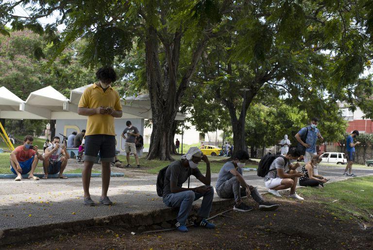 La gente se reúne en el Parque de los Mártires, donde funcionan las conexiones wifi, en La Habana, Cuba, el martes 13 de julio de 2021. (AP Foto/Eliana Aponte)