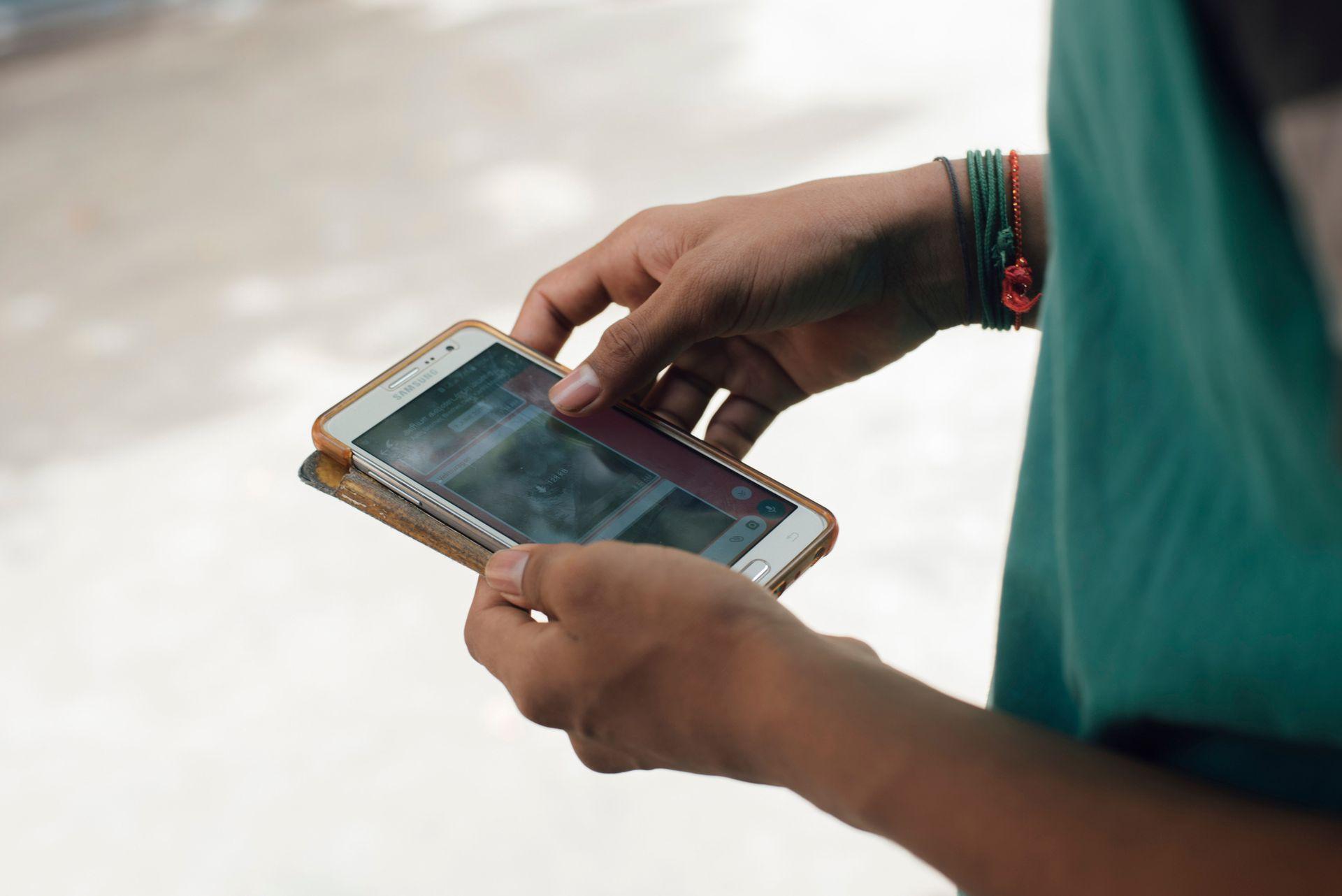 Un joven descarga un video desde la aplicación de WhatsApp