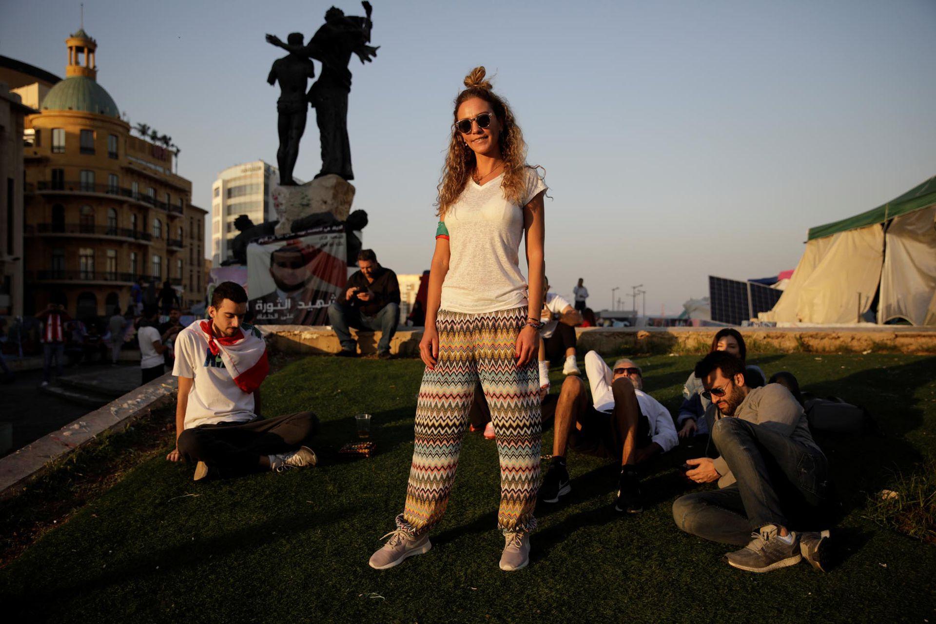 Hiba Ghosn, de 36 años, que trabaja en la industria de la moda junto a sus amigos sentados al sol de la tarde en la plaza de los Mártires, mientras la gente se reúne para una manifestación durante las protestas contra el gobierno en curso en Beirut, Líbano, el 17 de noviembre de 2019.