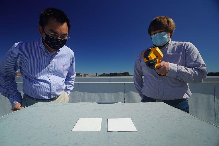 Los investigadores Xiulin Ruan y Joseph Peoples utilizan una cámara infrarroja para comparar el rendimiento de la pintura especial reflectante
