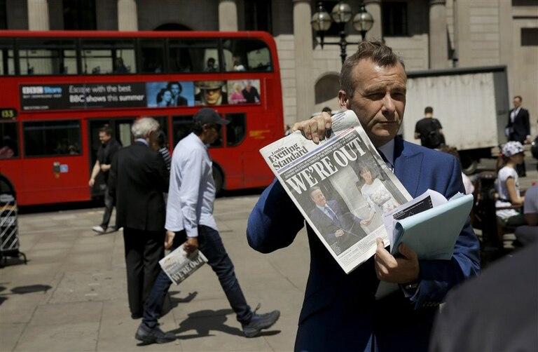 Un periodista muestra la tapa de un diario frente a la sede del Banco de Inglaterra, ayer, en Londres