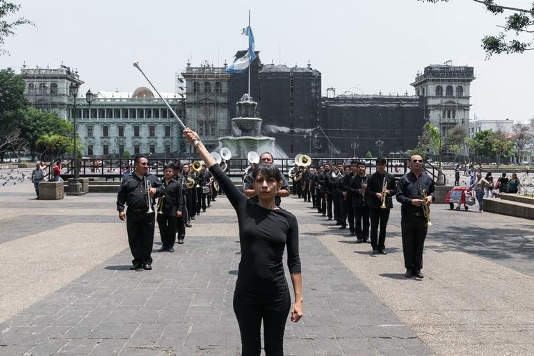 """En el registro de la performance """"El gran retorno"""" (2019), los músicos militares visten de negro y siguen el bastón de mando de Galindo"""
