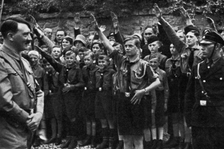 Adolf Hitler camina delante de un grupo de niños de las Juventudes Hitlerianas