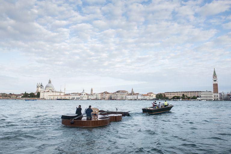 El violín de Noah es remolcado desde la laguna hasta el Gran Canal para su viaje inaugural; construido por artesanos locales, establece un rumbo para la esperanza y el resurgimiento creativo de los venecianos