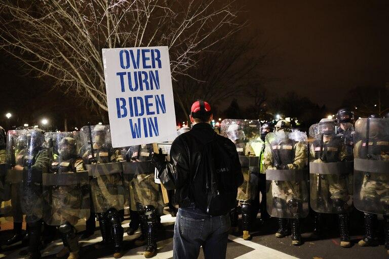 """Manifestante en las afueras del Capitolio con un cartel que lleva escrito """"den vuelta la victoria de Biden""""."""