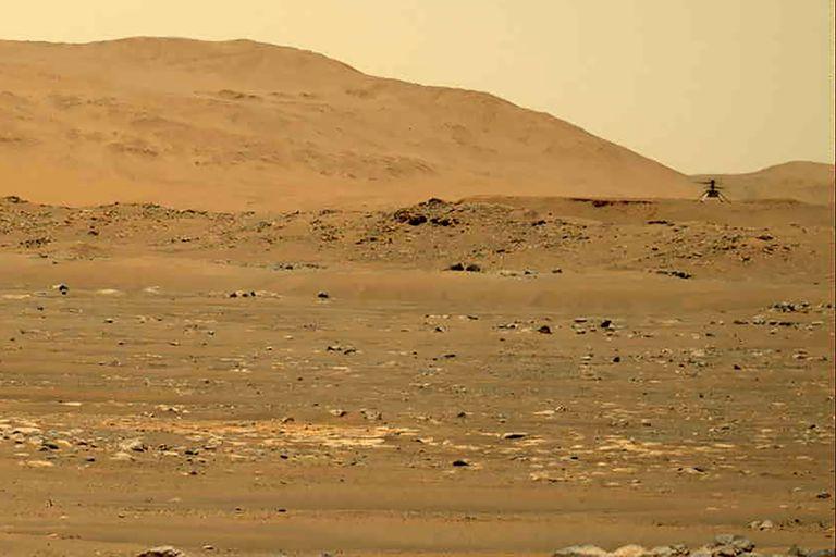 En esta imagen del 30 de abril de 2021 tomada por la sonda Mars Perseverance y difundida por la NASA, se ve al helicóptero Mars Ingenuity, a la derecha, sobrevolando la superficie del planeta. (NASA/JPL-Caltech/ASU/MSSS via AP, Archivo)