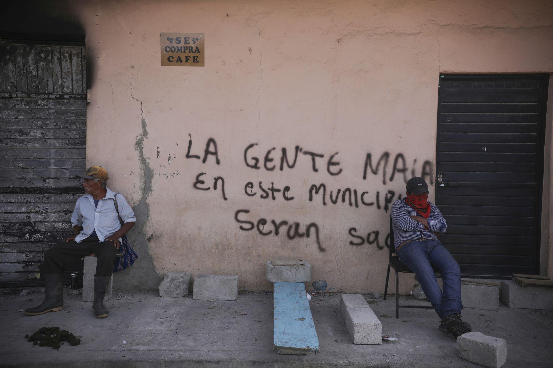 """Integrantes del grupo de autodefensas conocido como """"El Machete"""" se sientan junto a un grafiti"""