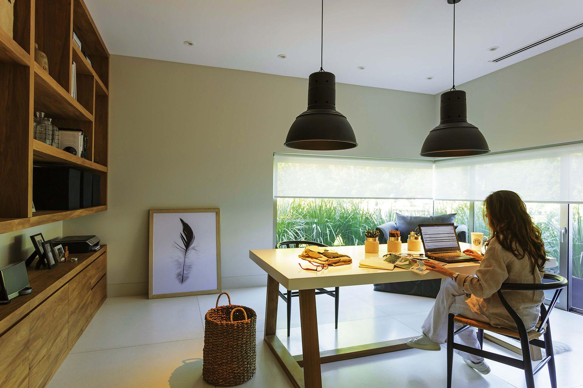 Sillas 'Wishbone' negras, biblioteca 'Iguazú' en petiribí, lámparas galponeras, escritorio con tapa blanca y base de petiribí, sillón individual 'Mercer' tapizado en tussor. (todo de Flora Home Bs As).