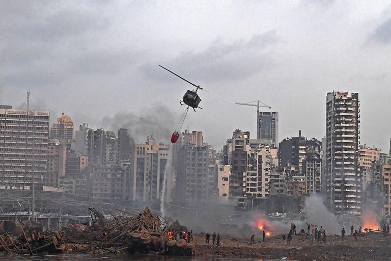 Un helicóptero intenta apagar varios incendios en la escena de la explosión masiva
