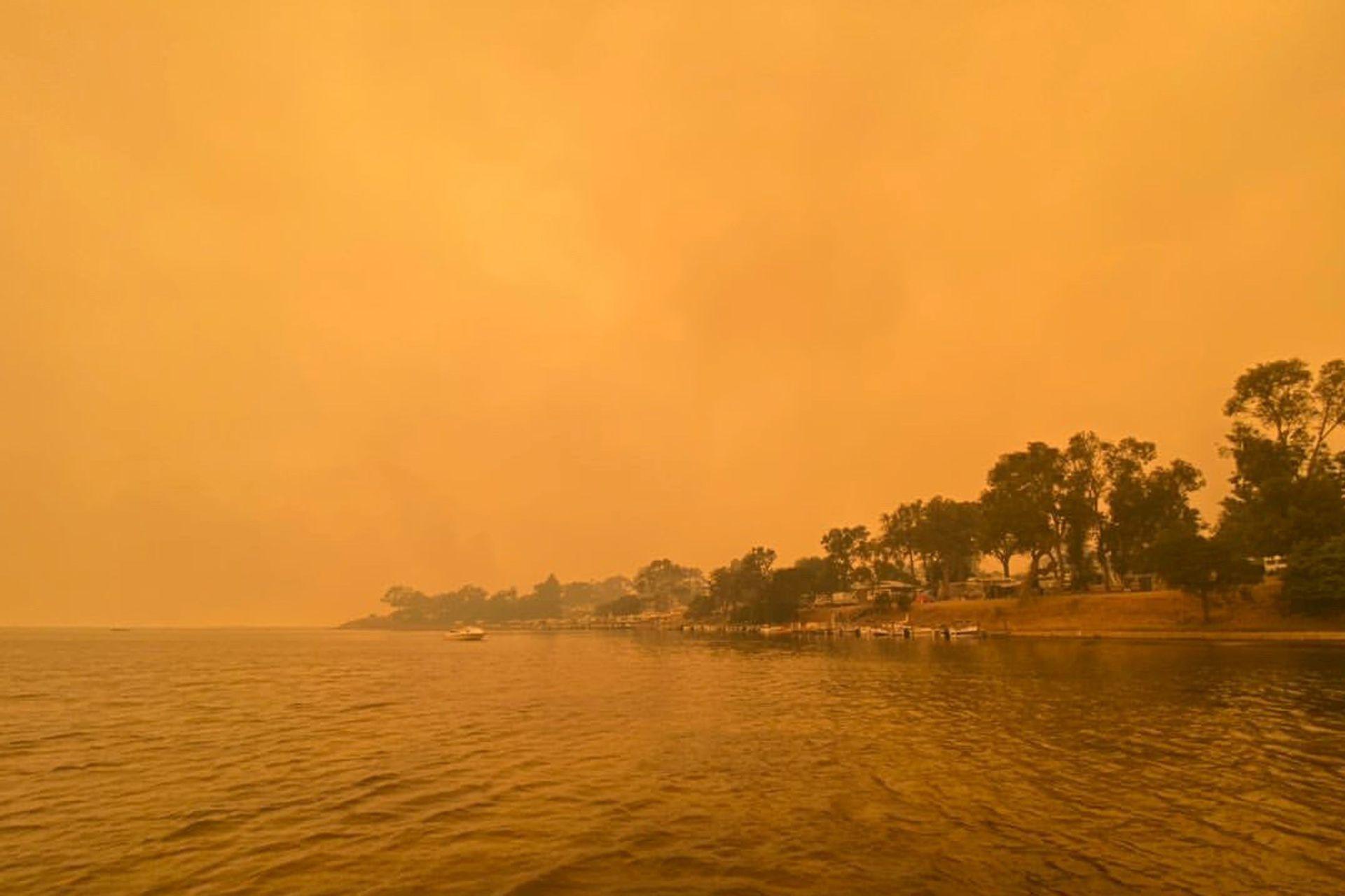 El humo de los incendios forestales salvajes envuelve el cielo en Mallacoota, Victoria, Australia, el 31 de diciembre de 2019. Las informaciones de varias zonas turísticas dan cuenta de miles de turistas y lugareños que pasaron la Nochevieja a orillas del mar, acorralados por las llamas.