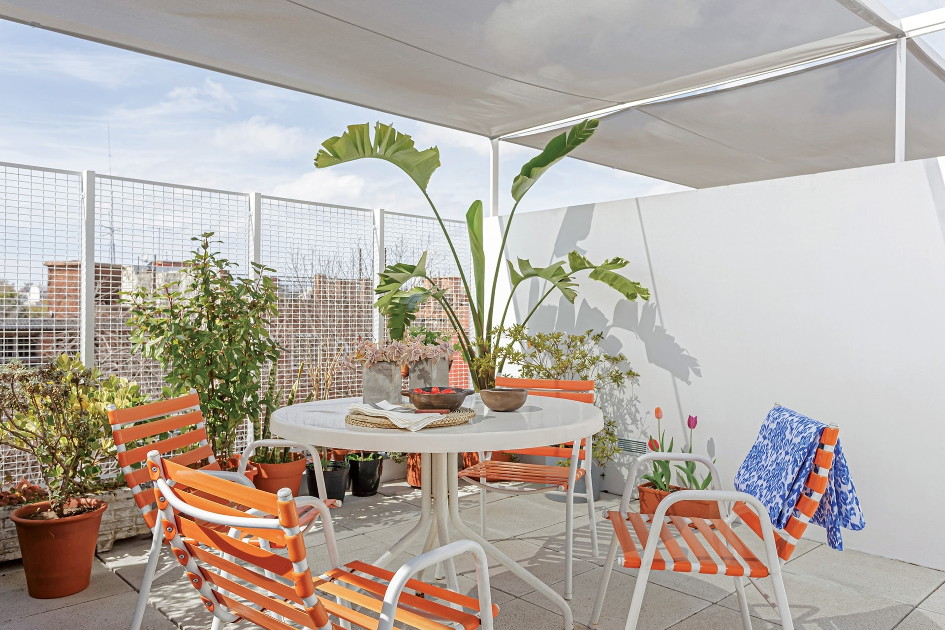 La media sombra suaviza el sol que llega directo. Sobre la mesa, individuales de ratán y servilletas de algodón (Claudia Adorno).