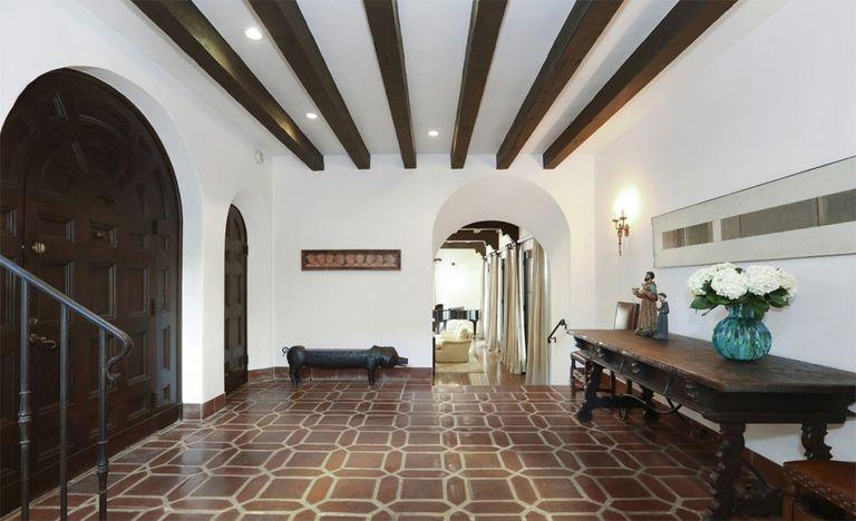 El salón de entrada, con vigas decorativas, paredes blancas y pisos de baldosas al mejor estilo colonial (Redfin)