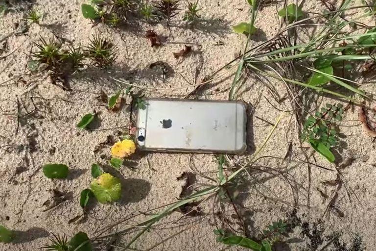 El iPhone 6S, recuperado al día siguiente tras la caída desde 300 metros, en la arena, cerca del mar y con una carga mínima de la batería