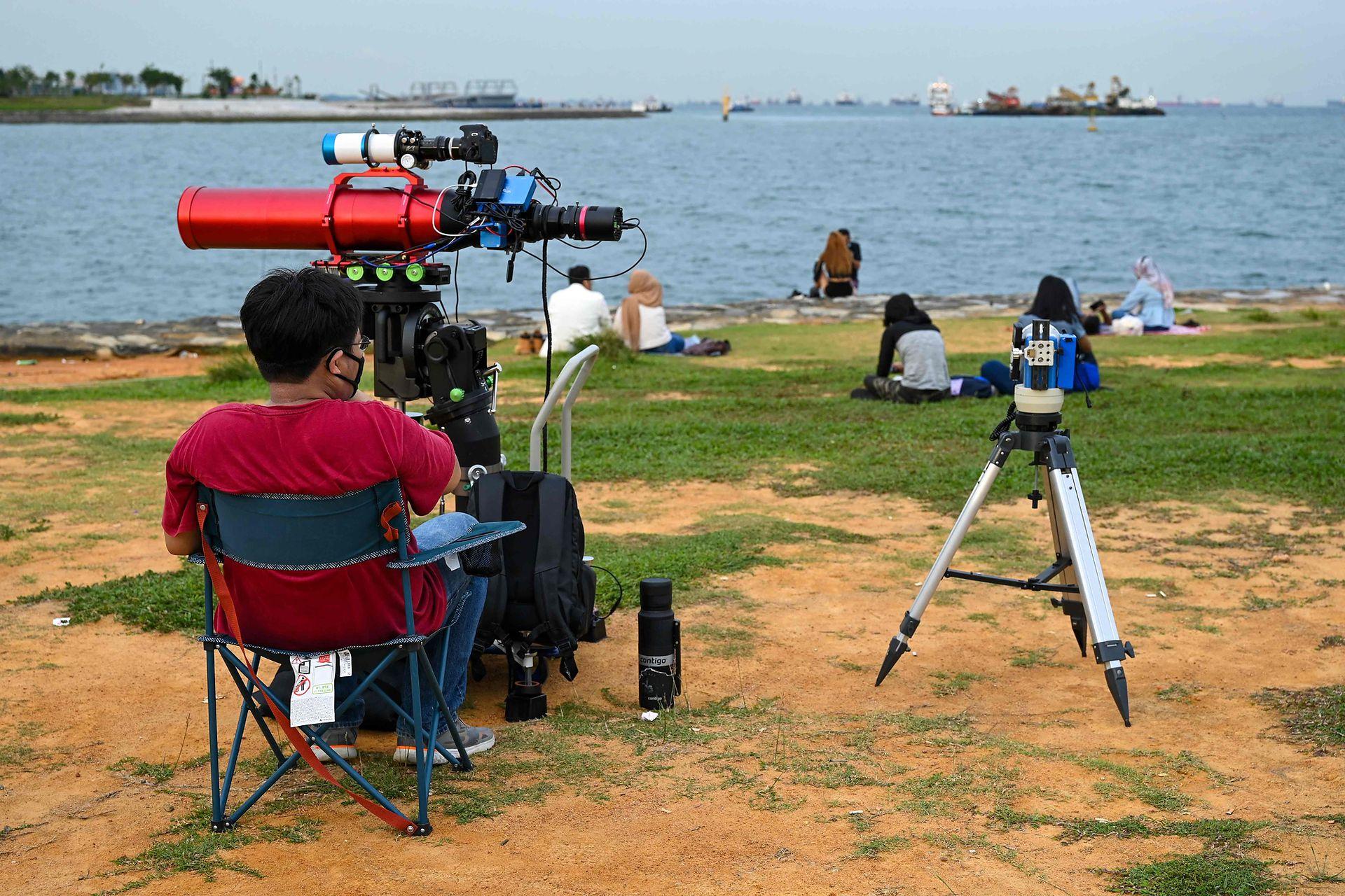 Un hombre con su telescopio espera la salida de la luna en Singapur