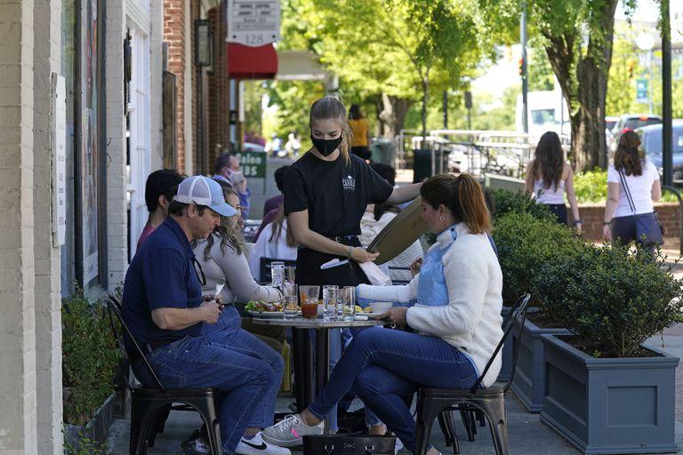 Comensales son asistidos en un café en Franklin Steet, en Chapel Hill, Carolina del Norte, el 16 de abril del 2021. Los consumidores estadounidenses absorbieron otro aumento de precios en mayo _ un incremento de 0,6% respecto a abril y de 5% en el último año, el mayor aumento de la inflación para 12 meses desde el 2008. (AP Foto/Gerry Broome)