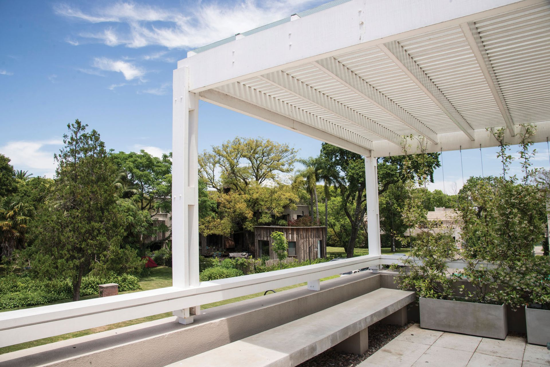 Pérgola que genera sombra inmediata y permite el uso de la terraza como expansión del salón de usos múltiples.