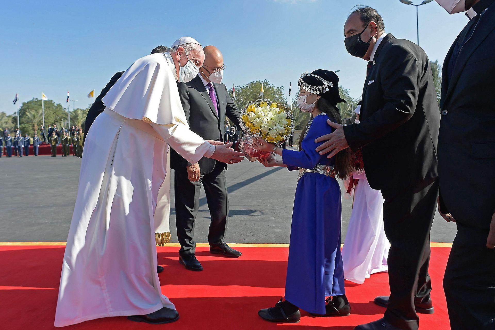 Una niña con vestimenta tradicional le ragala flores al Papa