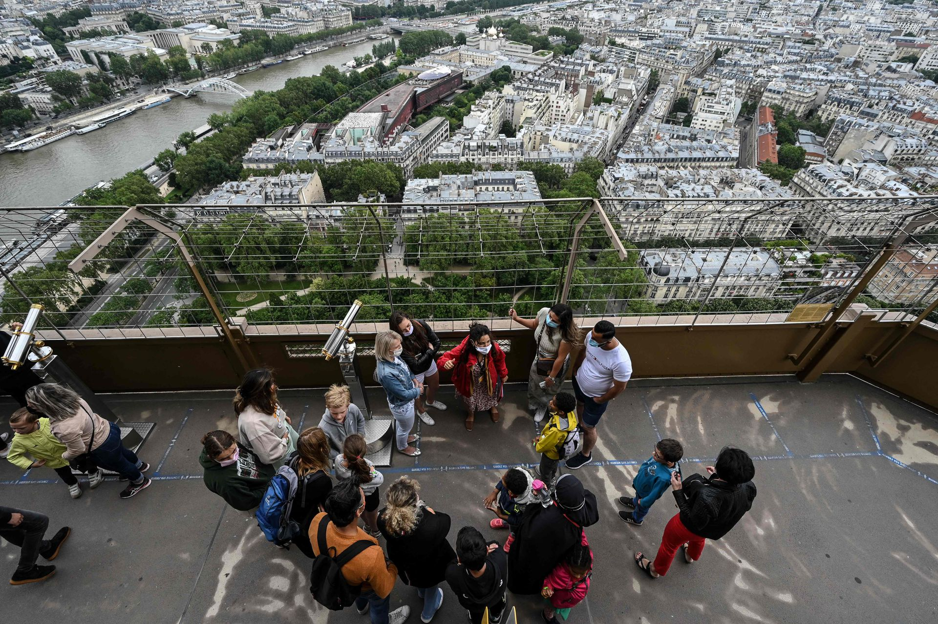 Visitantes en el primer piso de la Torre Eiffel, detrás la hermosa vista de París