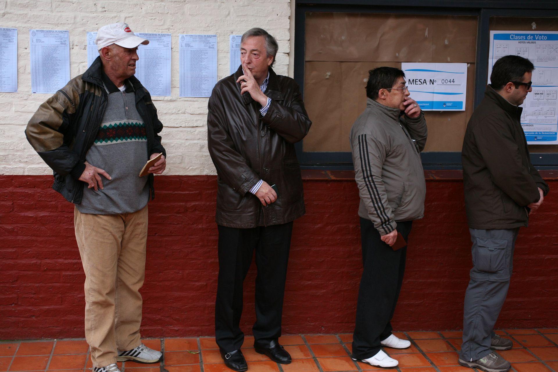 El expresidente Néstor Kirchner pide silencio a los periodistas mientras espera en la fila para emitir su voto en las elecciones legislativas de 2009