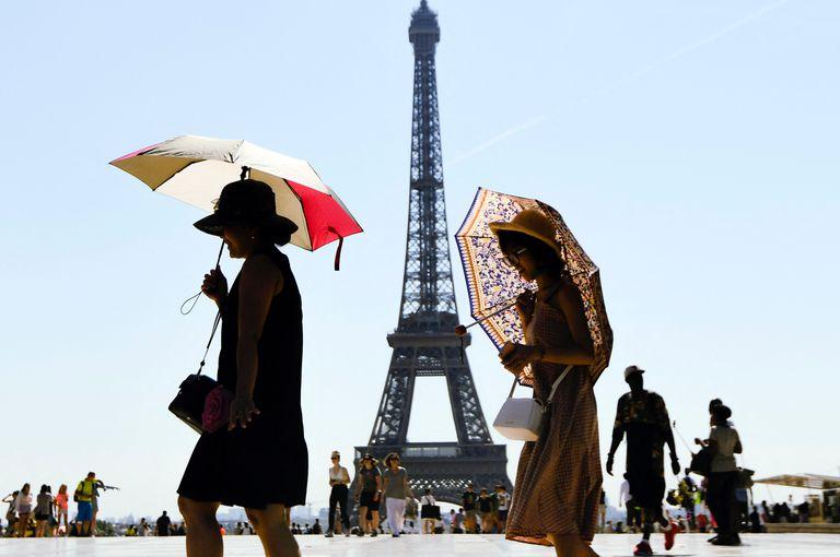 Turistas frente a la Torre Eiffel (Photo by ALAIN JOCARD / AFP)