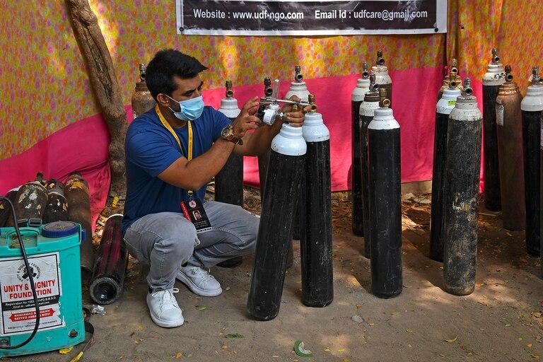 Shahnawaz Shaikh verifica la presión de un cilindro de oxígeno en un centro de distribución en un barrio pobre de Bombay