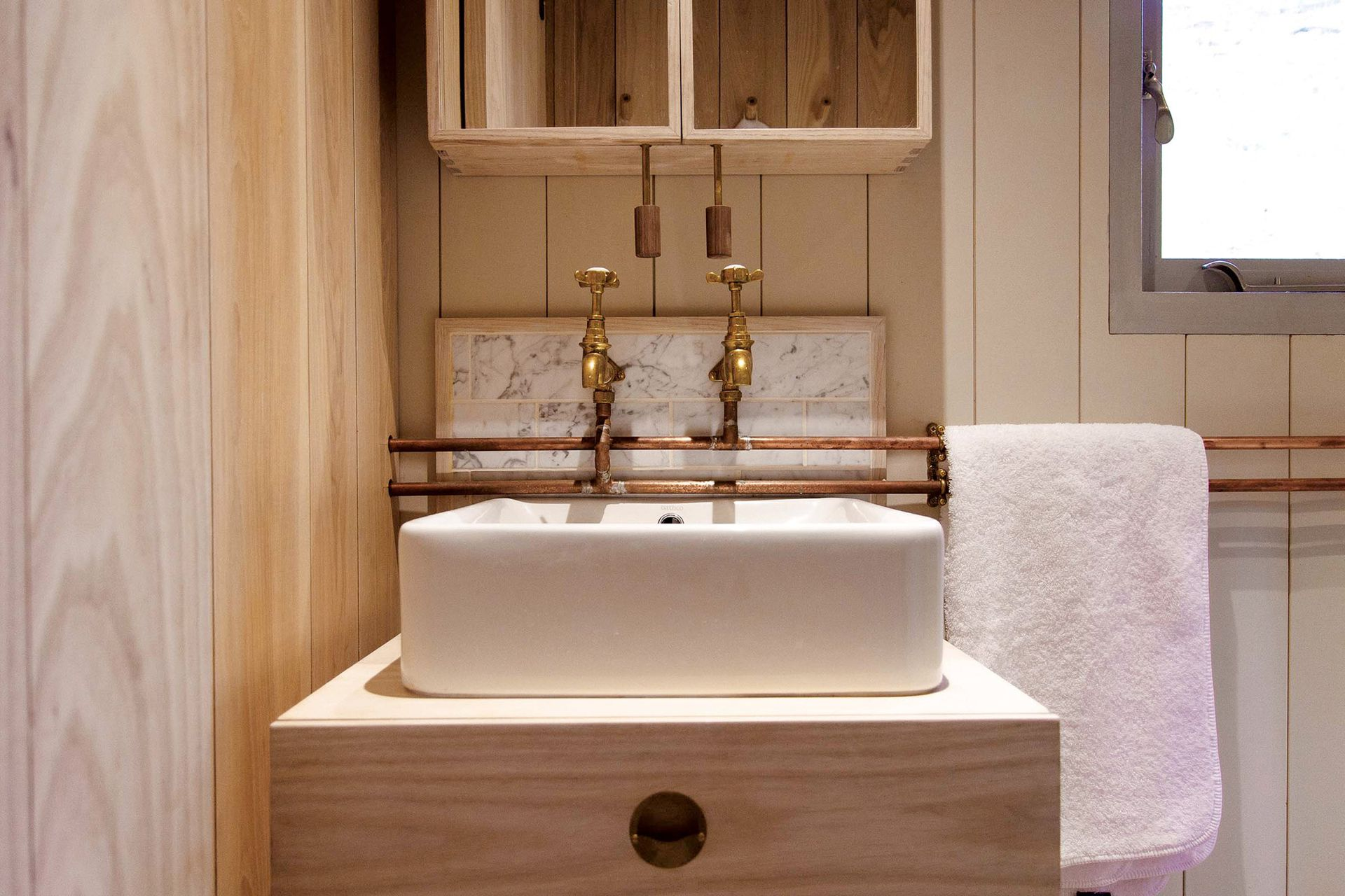 En el baño, bacha rectangular sobre un mueble de madera.