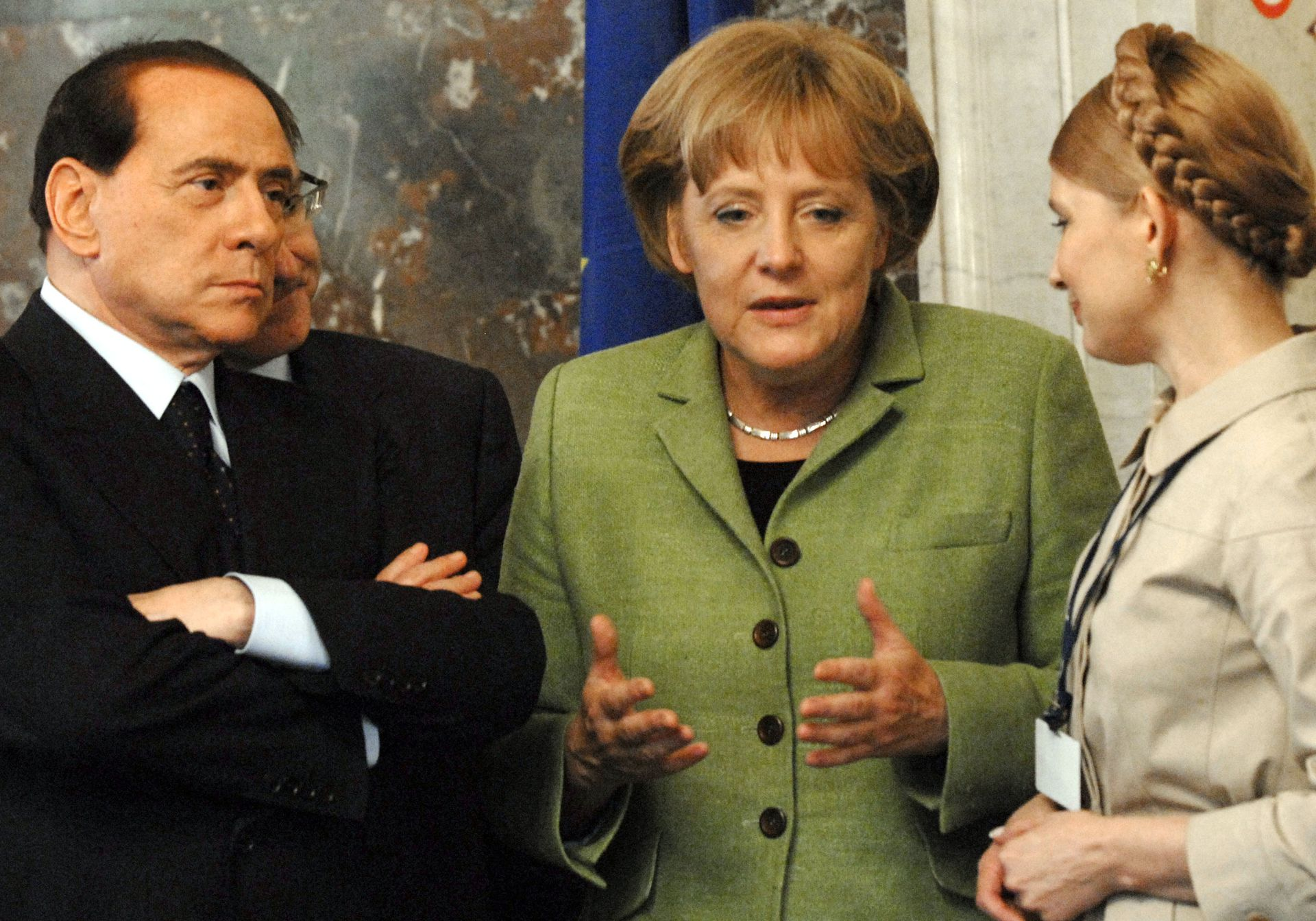 El primer ministro italiano, Silvio Berlusconi, escucha mientras la canciller alemana Angela Merkel, en el centro, habla con la primera ministra de Ucrania, Yulia Tymoshenko, durante una reunión del Partido Popular Europeo en Bruselas, el jueves 19 de junio de 2008