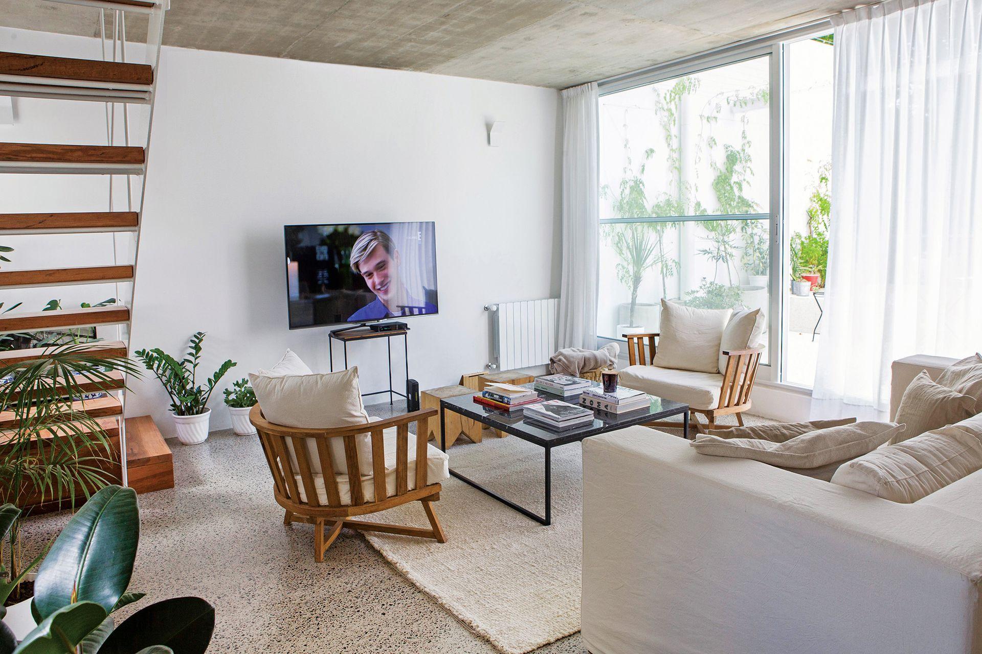 Sillón de dos cuerpos (Mema Lerena), dos sillones 'Gervasoni' (Maifren Muebles) con asiento tapizado en tussor off white y almohadones con funda de lino. Los tacos 'Álamo' (Net Muebles) cubren el otro lateral de la mesa. La alfombra, de lana (Elementos Argentinos), termina de marcar el espacio.