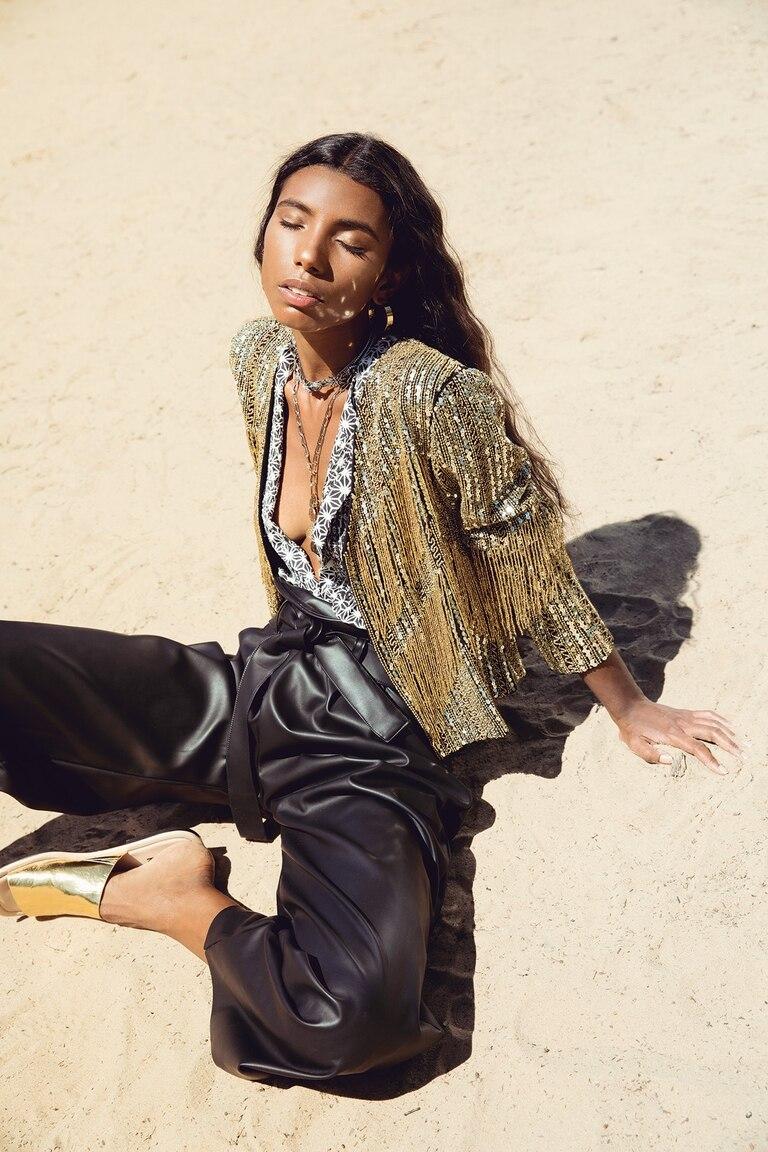 Camisa de lino y chaqueta bordadas con lentejuelas, collar choker de strass y colgante con monedas (Rapsodia), argollas doradas (Renner), pantalón de cuero negro con lazo y suecos de cuero dorados (Mishka)