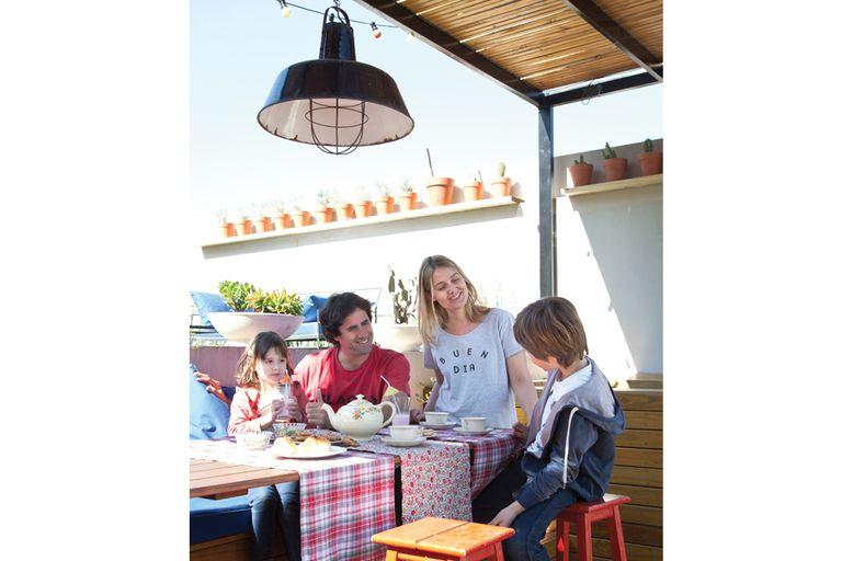La familia, a pleno, disfruta de tomar la merienda en el patio. La mesa larga ($5999 aprox) y las banquetas son de Easy