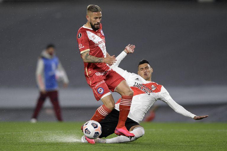 Miguel Ángel Torren y Matías Suárez en el partido de la semana pasada por la Copa Libertadores; se nota el agua acumulada en el campo de juego, aunque no llovió torrencialmente