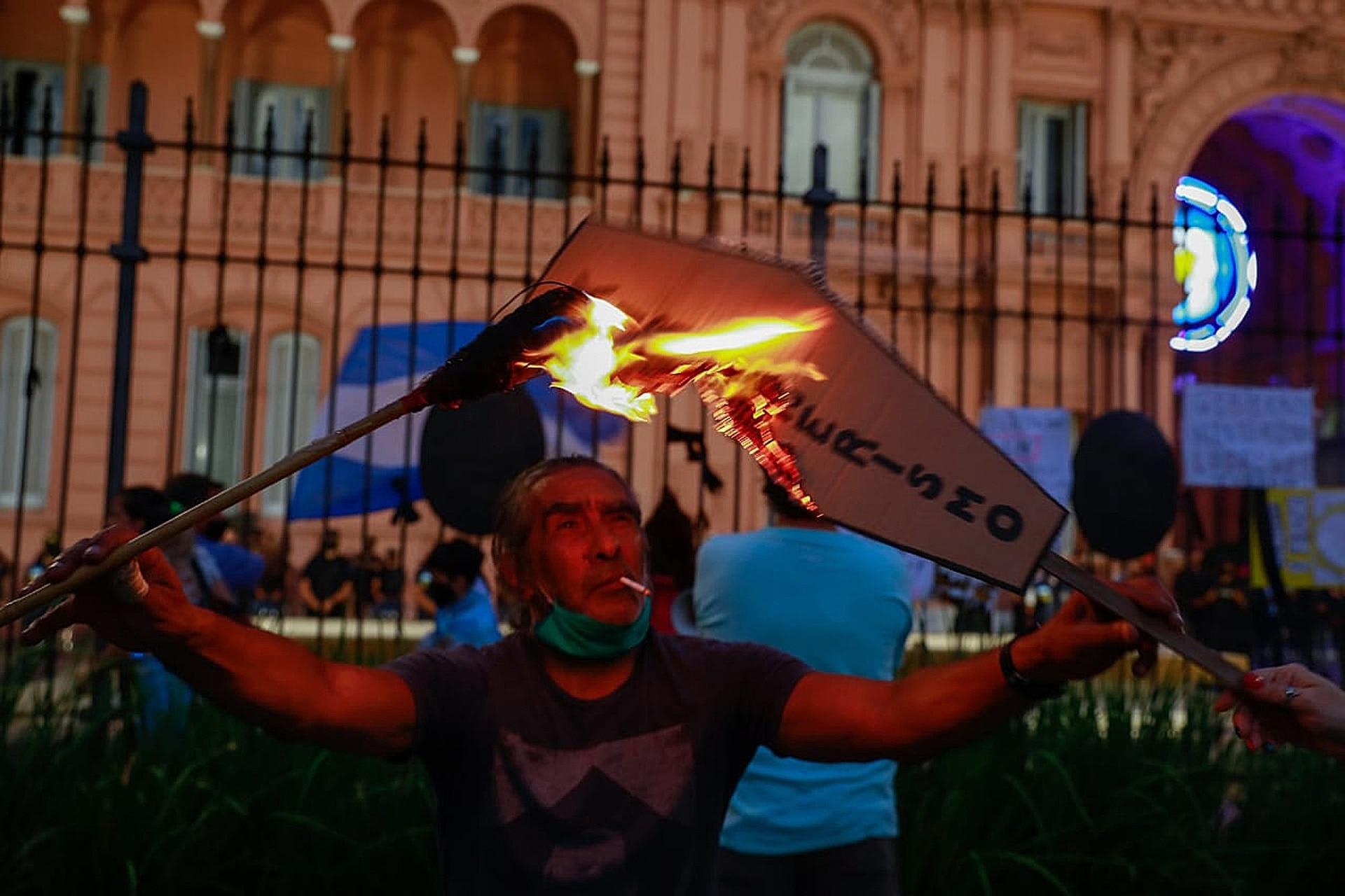 Un manifestante incendia un cartel frente a la Casa Rosada durante la manifestación por el 27F