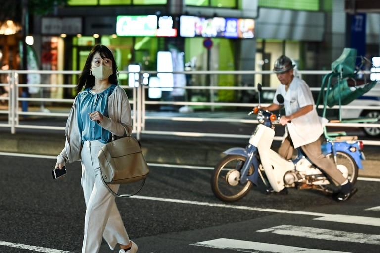 Esta foto tomada el 14 de septiembre de 2020 muestra a una mujer con tapabocas cruzando una calle de noche en Tokio