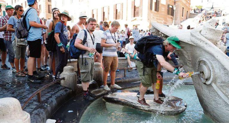 Filas de turistas llenan sus botellas en la Plaza de España, de Roma, para combatir la ola de calor
